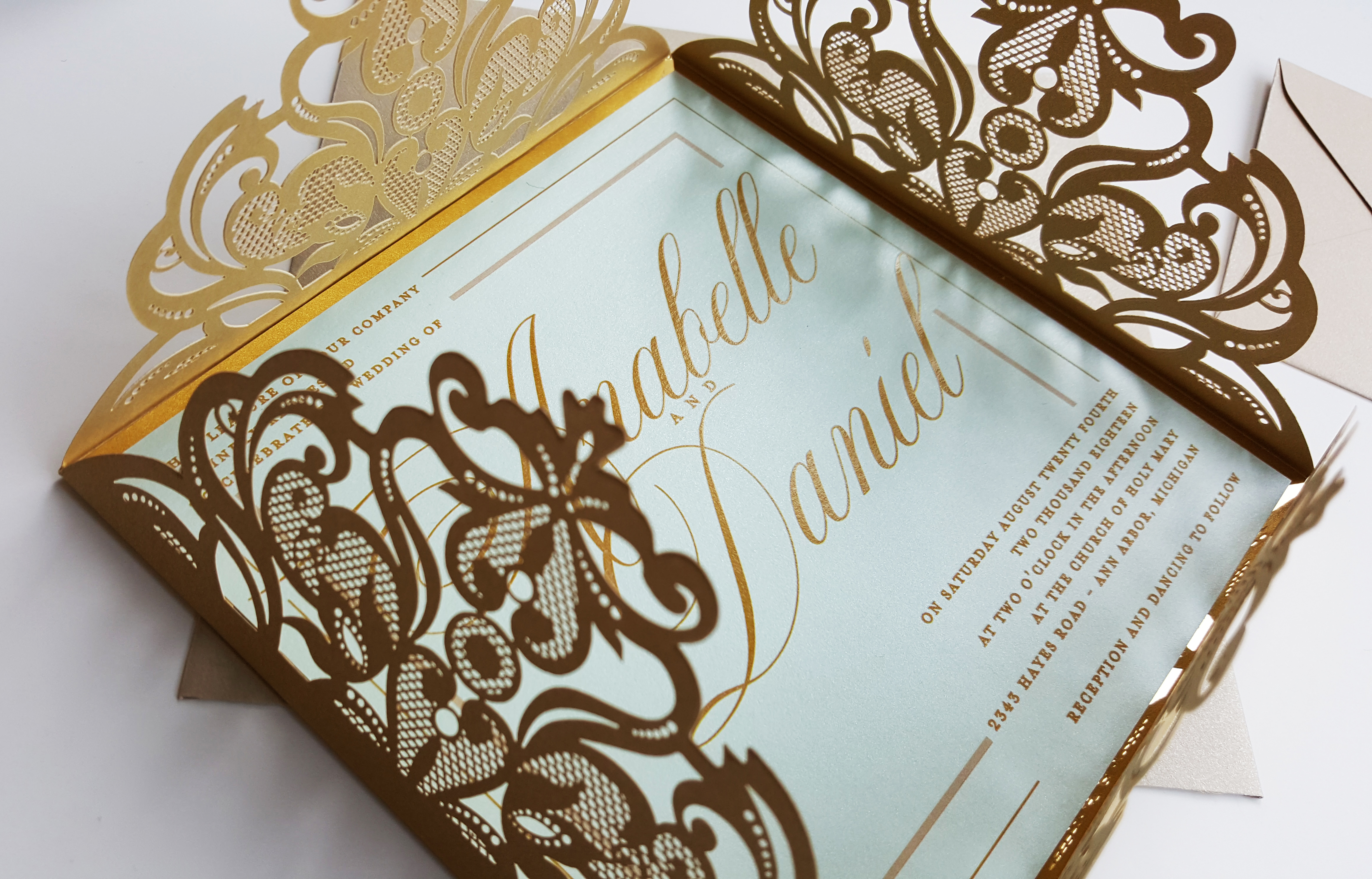 Gold laser cut wedding invitation with mint and gold mirror layers
