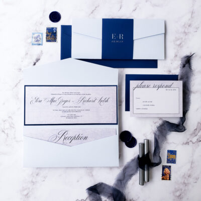 flatlay white envelope with blue bellyband and blue border