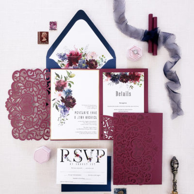 flatlay blue and maroon envelope with pattern and ribbon