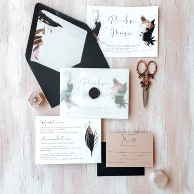 black envelopes with feather design and vintage scissors
