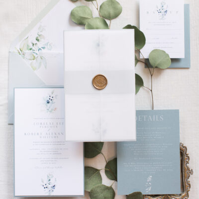 blue and white invitations with gold seal