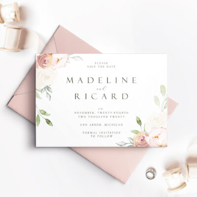 pink envelope with white save the date card and pink roses with leaves
