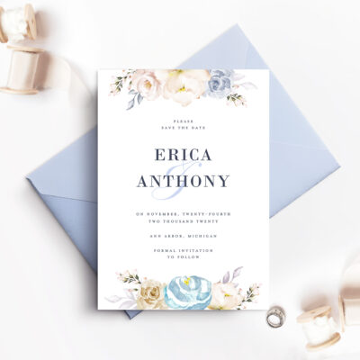 pale blue envelope with white save the date card and flowers