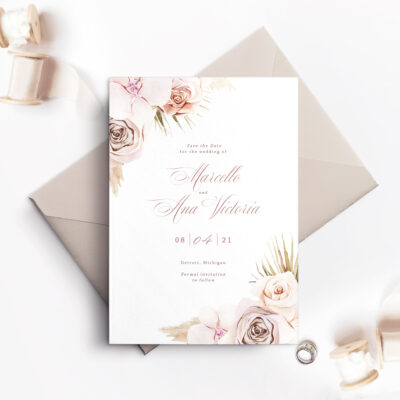 light pink envelope with white save the date card and pink flowers